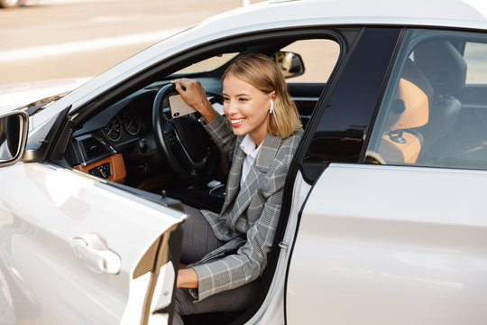 Photo of smiling businesswoman using earpod while getting out of car