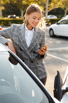 Photo of businesswoman using earpod and cellphone while leaning on car