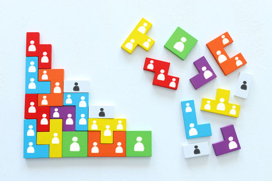 Business concept image of tangram puzzle blocks with people icons over wooden table, human resources and management concept
