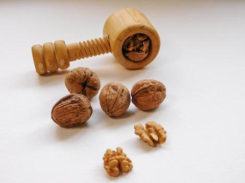 Casse-noix artisanal en bois qui casse une noix avec noix et cerneaux