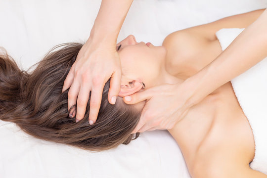 massage and stretching of the cervical muscles. Beautiful girl gets massage in a spa salon. light tones photos. concept of massage and health. rheumatism, arthrosis
