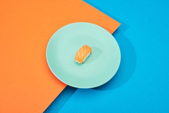 fresh nigiri with salmon on blue and orange surface
