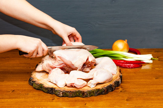 Cook chef hands woman cuts carcass of whole chicken on a wooden background.