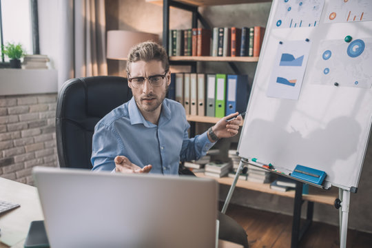 Young bearded man in eyeglasses making presentation online