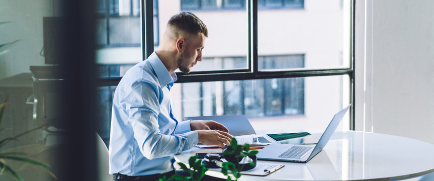 Serious entrepreneur reviewing contract while working in office
