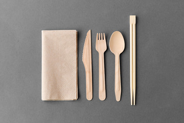 cutlery, recycling and eco friendly concept - wooden disposable spoon, fork, knife with chopsticks and paper napkin on grey background