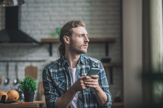 Thoughtful young man using his smartphone at home