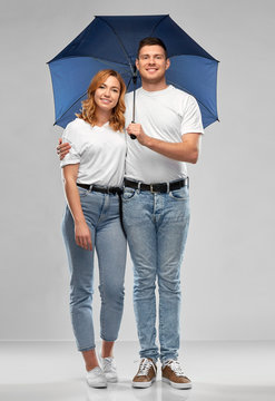 weather, relationships and protection concept - portrait of happy couple in white t-shirts with umbrella over grey background