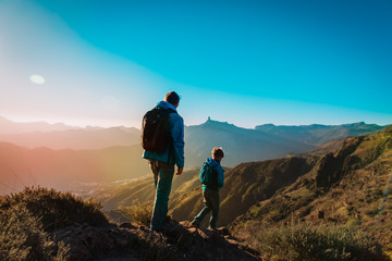 father and son hiking in sunset mountains, family travel