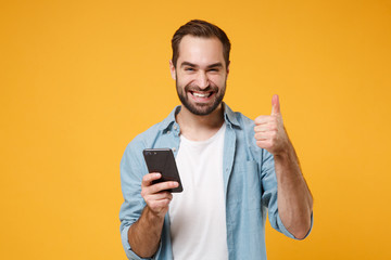 Smiling young man in casual blue shirt posing isolated on yellow orange wall background in studio. People lifestyle concept. Mock up copy space. Using mobile phone typing sms message showing thumb up.