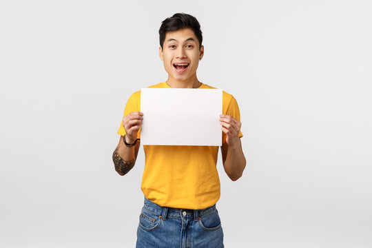 Enthusiastic, thrilled handsome chinese guy with tattoos, holding sign, blank piece paper over chest, promote company offer, smiling with rejoice and happiness, standing white background advertise