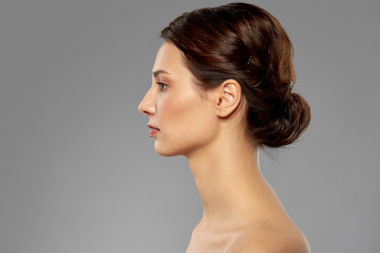 beauty, bodycare and people concept - profile of beautiful young woman with bare shoulders over grey background