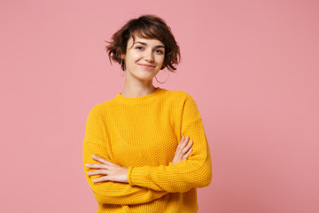 Smiling young brunette woman girl in yellow sweater posing isolated on pastel pink background studio portrait. People sincere emotions lifestyle concept. Mock up copy space. Holding hands crossed.