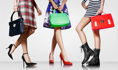 Wall Mural - Fashion shopping image. 3 women with beautiful purses and shoes standing together.