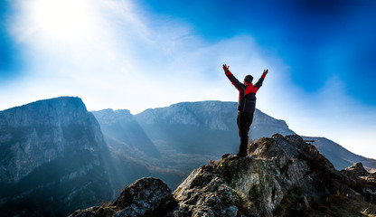 Adventurous man is standing on top of the mountain and enjoying the beautiful view. A man stands on the edge of a cliff in Sicevo Gorge, Serbia. Travel Lifestyle emotional concept Fotomurales