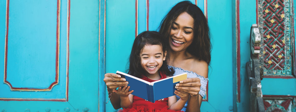 Young laughing Asian lady with daughter on knees reading book