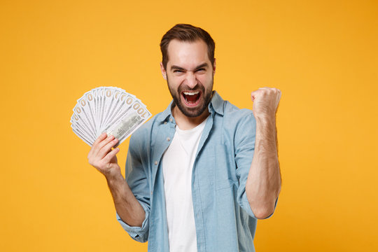 Crazy young man in blue shirt posing isolated on yellow orange background. People lifestyle concept. Mock up copy space. Holding fan of cash money in dollar banknotes, doing winner gesture, screaming.