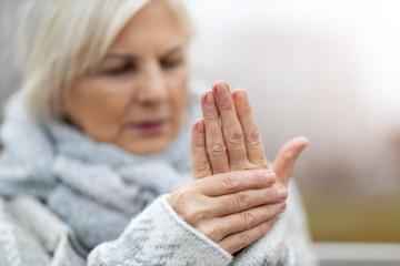 Senior woman with arthritis rubbing hands