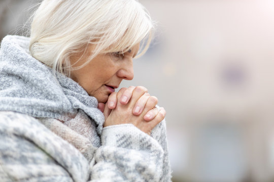 Portrait of senior woman praying