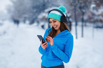 Young sports woman enjoys music after jogging  on snowy day in the city