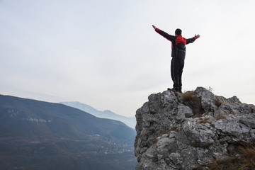 Adventurous man is standing on top of the mountain and enjoying the beautiful view. A man stands on the edge of a cliff in Sicevo Gorge, Serbia. Travel Lifestyle emotional concept