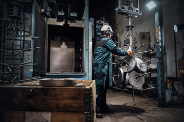 Foto op Aluminium Imagination Worker in helmet is putting freshly made metal weight to the storage at metal factory.