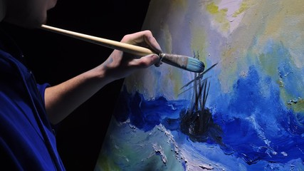 Artist copyist paint seascape with ship in ocean. Craftsman decorator draw as boat sail on blue sea with acrylic oil color. Draw finger, brush, knife palette. Indoor. Dark magic cinematic look. Wall mural