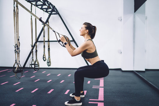 Sportive woman squatting with TRX loops