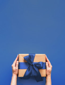Female hands hold gift box on deep blue background with copy space for design. Caucasian girl hands holding gift box in craft wrapping paper with fashion color 2020 blue satin ribbon. Vertical.