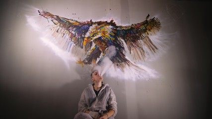 Artist designer draws an eagle on the wall. Craftsman decorator paints a picture with acrylic oil color. Vaper smokes vape. Painter painter dressed in a paint coat. Indoor. Dark magic cinematic look.