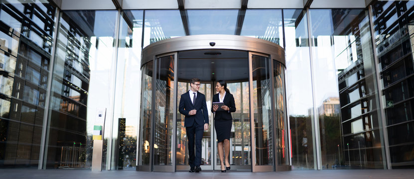 Smiling young coworkers talking on street Contemporary elegant businesswoman with tablet talking to male colleague while walking out of modern office building with glass revolving doors