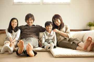 ソファに並んで座る家族