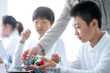 先生にプログラミングの勉強を教わる小学生