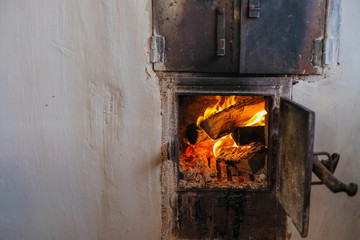 Traditional wood burning stove in the Ukrainian village. Fire in the furnace. Copy space.