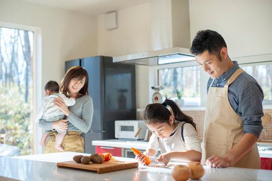 キッチンで料理をする家族を見守る母親