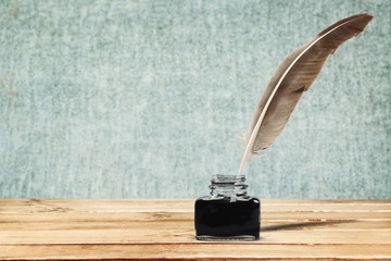 Feather quill pen and glass inkwell on background