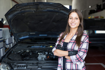 Casual woman in checkered shirt and gloves holding arms crossed and smiling at camera, working in car service