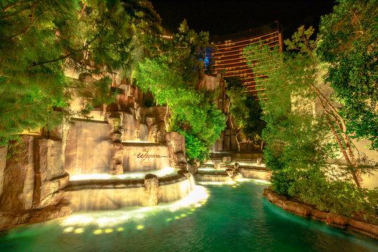 Las Vegas, Nevada, United States - August 18, 2018: Wynn Las Vegas Waterfall Fountain. The Wynn is Resort Hotel 5-star casino in Las Vegas Strip. Falls in the garden outdoors illuminated by night.