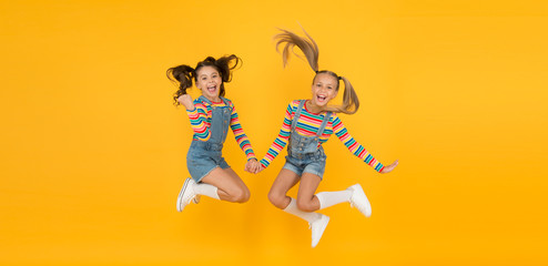 party fun time. little girls jump yellow wall. sense of freedom. finally summer vacation. free and energetic beauty. happy childhood. real friendship. best friends forever. small sisters have fun