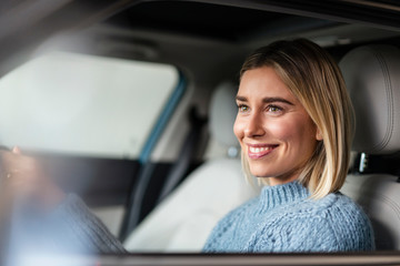 Portrait of smiling young woman driving a car
