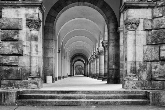 Greyscale shot of a concrete ancient building with a long hallway