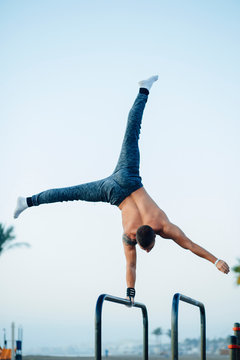 Young man practicing calisthenics at an outdoor gym