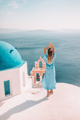 Young woman with blonde hair and blue dress in oia, santorini, greece with ocean view and churches