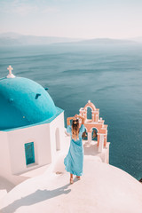 Fototapeten Santorini Young woman with blonde hair and blue dress in oia, santorini, greece with ocean view and churches