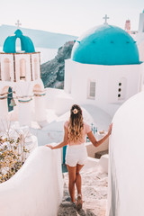 Poster Santorini Young woman with blonde hair walking in oia santorini
