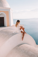 Foto auf Leinwand Santorini Young woman with white dress on rooftop in santorini greece