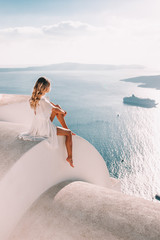Young woman with white dress on rooftop in santorini greece