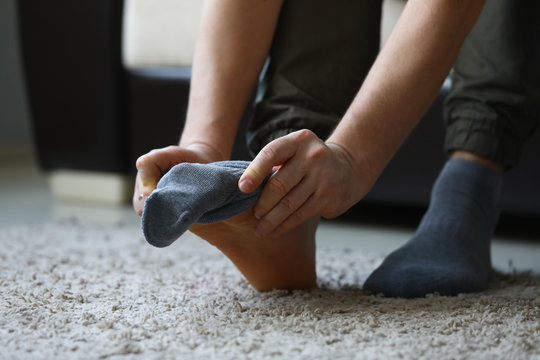Man at home in morning puts gray socks on his leg