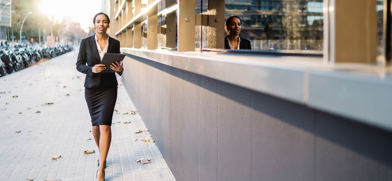 Black businesswoman with paper file on street