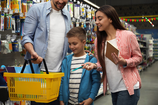 Family with little boy choosing school stationery in supermarket